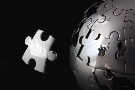 globe puzzle: Floating jigsaw peice over chrome puzzle globe Stock Photo