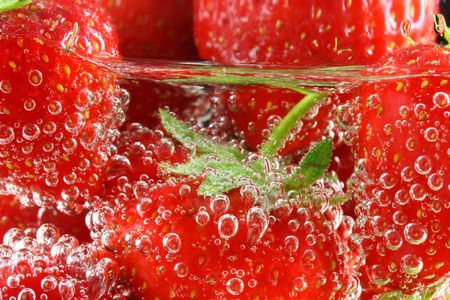 Strawberries in water with bubbles close up photo