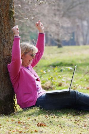 Women sitting against tree with laptop cheering photo