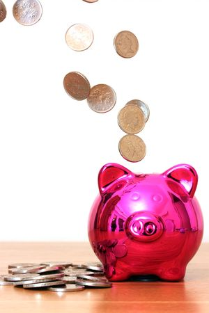 Piggy bank saving with money pouring into it Stock Photo - 6376494