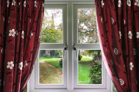 Window and curtains with view of a English church garden