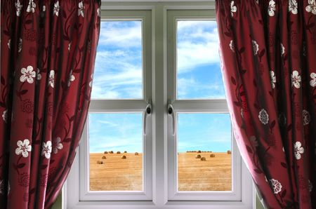 land locked: Window and curtains with view of hay bales and sky  Stock Photo