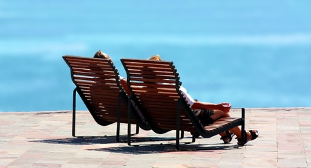 loungers: Couple lounging by the sea