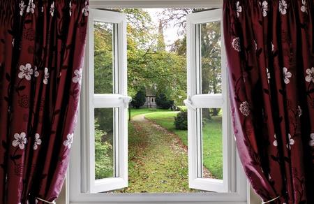 glasscheibe: Geöffnetes Fenster mit Vorhängen zu einem Kirchgarten