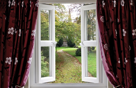 Open window with curtains to a church garden photo