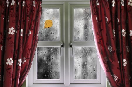 Rain on a window with curtains photo