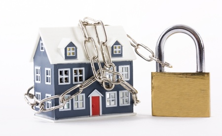lock and chain: House secured with chain and padlock on a white background Stock Photo