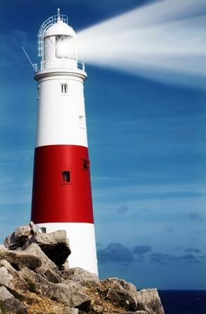 Faro en las rocas con haces de luz