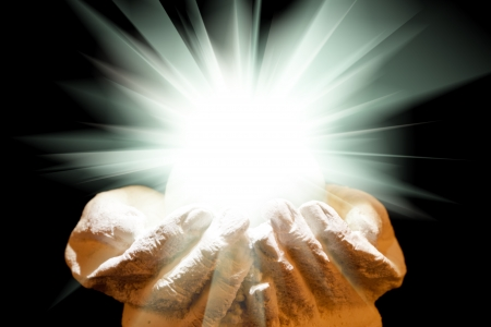 Spiritual light in cupped hands on a black background Stock Photo