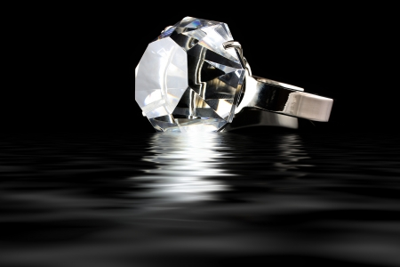 Diamond ring with water reflection on black background photo