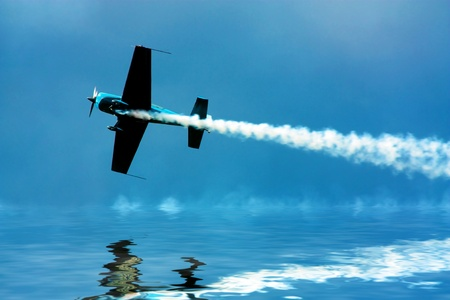Stunt plane flying close to water photo