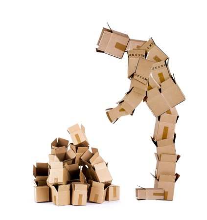 Box man looking at a pile of boxes Stock Photo
