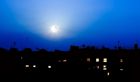 Night over London buildings with moon Stock Photo