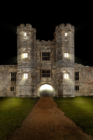 Old castle at night with lights shining through windows