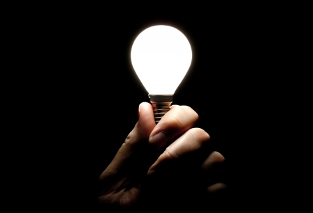 Lit lightbulb held in hand on black background 版權商用圖片