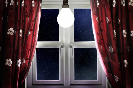 Light bulb shining in window with curtains photo