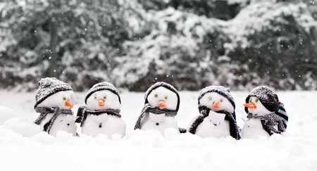 Little snowmen in a group carol singing in the snow photo