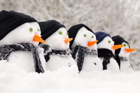 Snowmen close up in a row with hats and scarfs photo