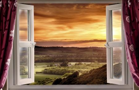 시골 풍경과 일몰 위에 열려있는 창을 통해보기