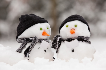 Two little snowmen in a group carol singing in the snow