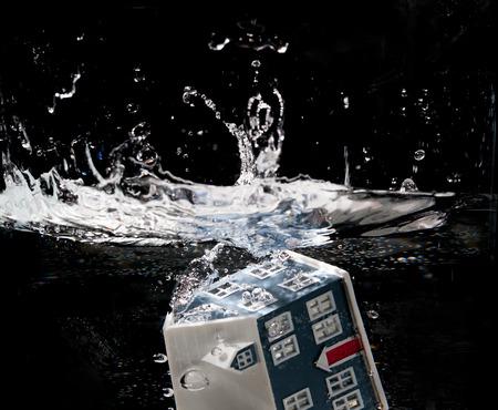 Toy house sinking underwater isolated on black  photo