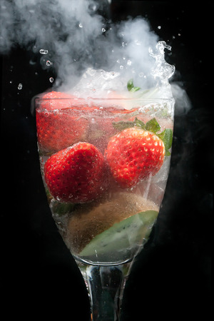 Cocktail of fruit in a glass exploding with steam and smoke, with water movement frozen, all on a black background photo