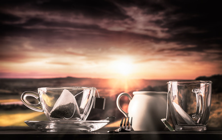 teatime: Glass cup and saucer with teabag and an amazing view of sunset