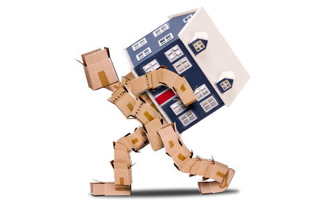 removals: Man made of boxes carrying a house on his back with a white background Stock Photo