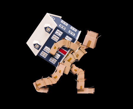 removals: Man made of boxes carrying a house on his back with a black background