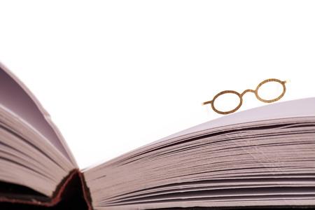 screenwriter: Occhiali da lettura di riposo sul bordo di un libro bianco aperto con pagine bianche e lo spazio per il testo