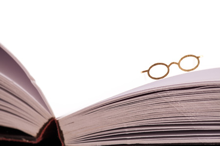screenwriter: Reading glasses resting on the edge of an open blank book with white pages and space for text