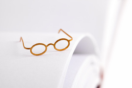 screenwriter: Reading glasses on a open blank book with white pages and space for text