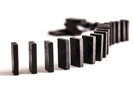 playtime: Black dominoes in a curved line ready to topple, on a white background