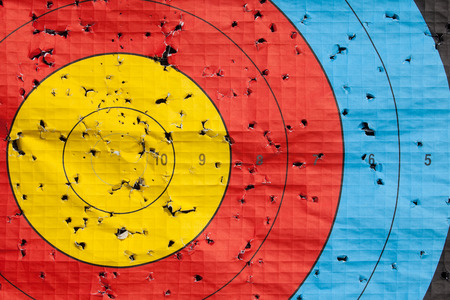 archery target: Archery target close up with many arrow holes in gold red blue and black