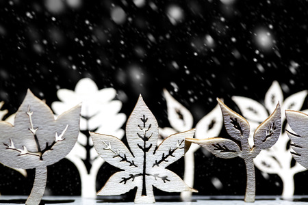 winter scene: Fantasy winter snow scene with a line of artistic white trees and leaf shapes all under a heave snowfall and night sky Stock Photo