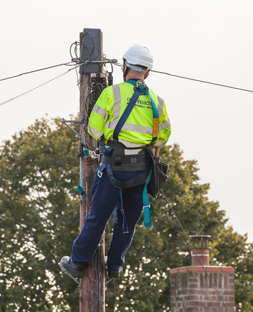 FAKENHAM, NORFOLK / UK - 10th OCTOBER 2016: Openreach BT engineer fixing cables up a pole. UK internet and telephone infrastructure provider at work providing internet and telephone services to rural locations