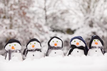 다섯 명의 귀여운 눈사람이 모두 겨울을 향한 옷을 입고 눈에 앉아있었습니다. 눈사람 모자와 스카프 입고 당근 코. 나무와 백그라운드에서 겨울 장면