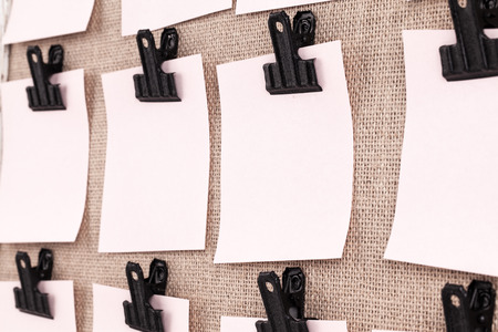 paper board: Notice board with clips holding blank square paper notes close up. Viewed at an angle