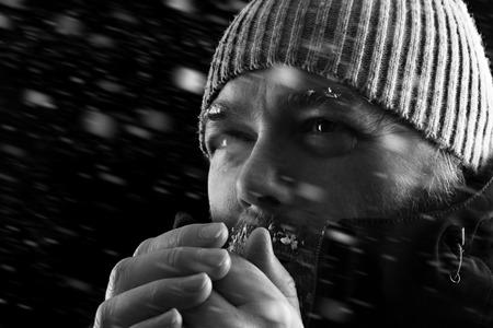 Hombre de congelación en frío de pie en una tormenta de nieve biazzard tratando de mantener el calor. El uso de un gorro y abrigo de invierno con escarcha y hielo en su barba y las cejas. En blanco y negro. Foto de archivo