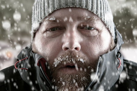 Congélation homme froid debout dans une tempête de neige de tempête de neige en essayant de garder au chaud. Le port d'un chapeau de bonnet et manteau d'hiver avec le gel et la glace sur sa barbe et les sourcils regardant fixement la caméra.