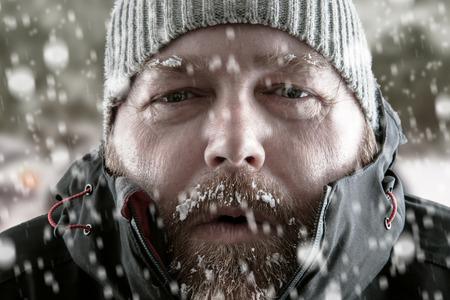 Mrozie mężczyznę stojącego w zamieci śnieżnych burz próbując ogrzać. Na sobie kapelusz czapka i płaszcz zimowy z mrozem i lodem na brodę i brwi patrząc na kamery.