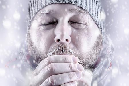 그의 손에 불어 따뜻하게 유지하려고 눈 폭풍 화이트 아웃 차가운 사람을 동결. 눈을 감고, 겨울 코트와 비니 모자를 착용. 그의 수염과 눈썹에 서리와