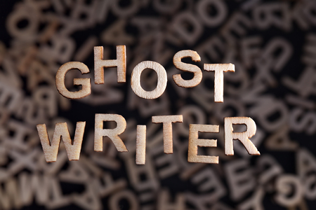 authors: Ghostwriter text in wooden letters floating above random letters out of focus Stock Photo