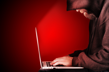 predator: Male computer hacker wearing a hooded top leaning over a laptop with red warning background. The screen light illuminates the man with a beard performing illegal activities. Graduated copy space on the left