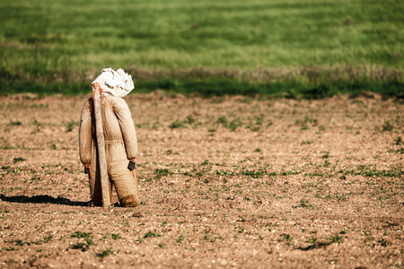 Scarecrow protecting the seeds in a newly ploughed field Stock Photo