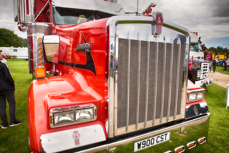 NORFOLK, UK - AUGUST 19th, 2017: Truckfest Norwich is a transport festival in the UK based around the haulage industry located in Norfolk. Including trade stands and shows like Monster Truck car crushing & stunt driving. Kenworth red truck front close up.