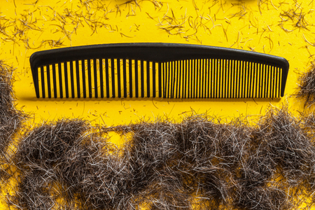 Comb and beard trimmings on a bright yellow background. Stock fotó