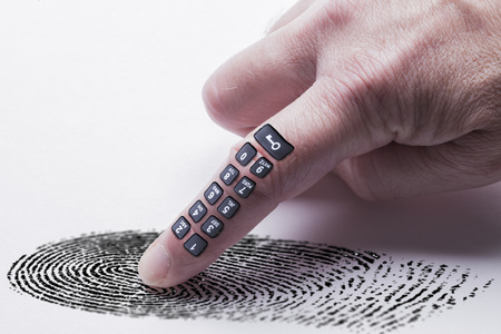 Digital finger print concept for online identity protection showing a finger with a keypad pressing on a finger print mark. White background Stock Photo
