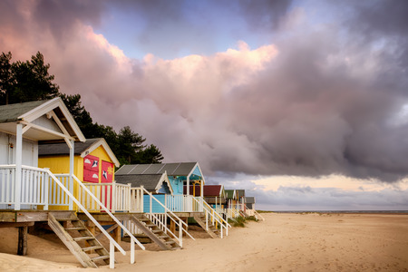 Elevated beach huts in Norfolk are some of the most colourful in England, situated on the sandy North Norfolk coast. Sunrise clouds with an early morning pink tint. Steps leading down the the sandy shoreline from the wooden beach huts. Norfolk has been awarded the most 'Blue Flags' for high quality beaches in the country.