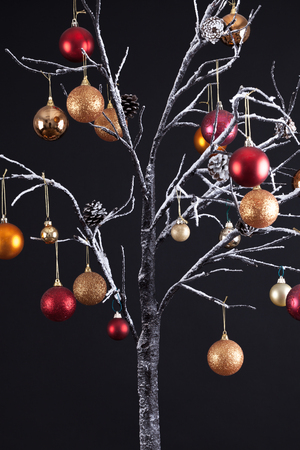 Modern Christmas tree with bare snow covered branches, decorated with hanging glitter balls, all on a black background Stock Photo